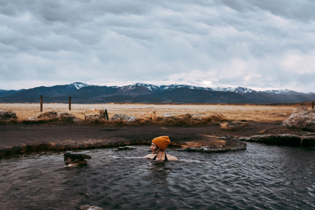 Gabi soaking in meadow natural hot springs in utah early morning photographed by the foxes photography adventure wedding photographers and outdoor lifestyle photography