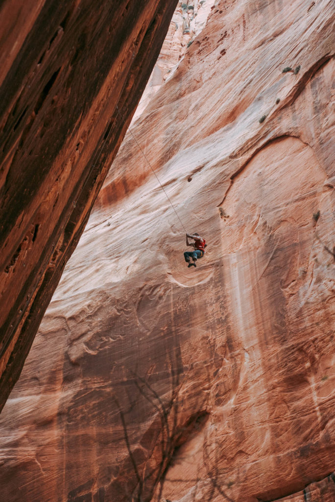 Climber taking a victory whipper Sport Climbing at Namaste Wall in Kolob Canyon Zion national park utah photographed by the foxes photography adventure wedding photographers and outdoor lifestyle photography
