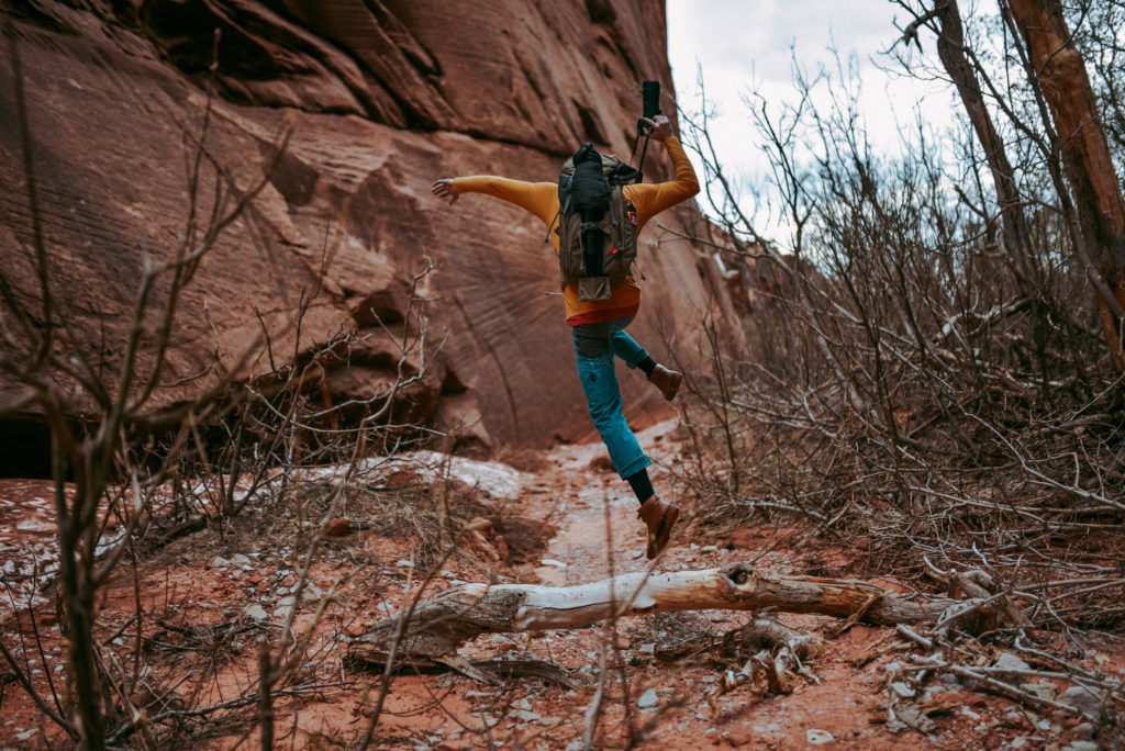 Brandon jumping over log Exploring and hiking in Kolob Canyon Zion national park utah photographed by the foxes photography adventure wedding photographers and outdoor lifestyle photography
