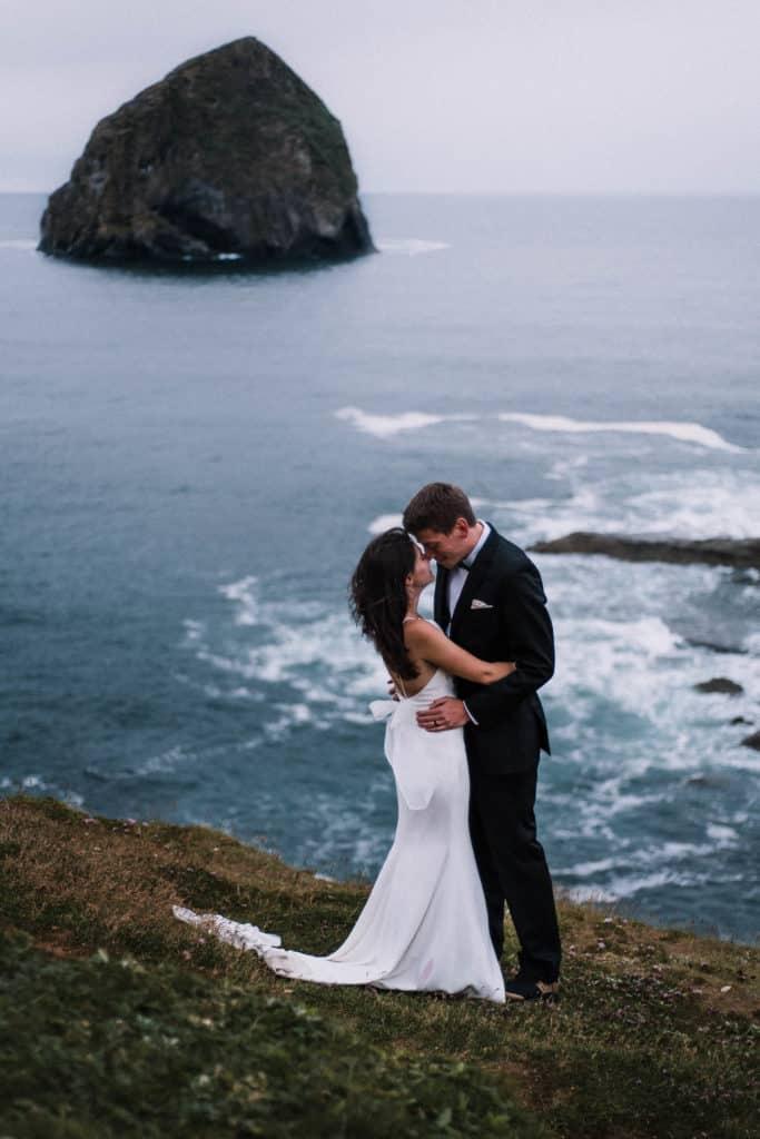 Bride and Groom standing by haystack Cape Kiwanda Oregon Coast