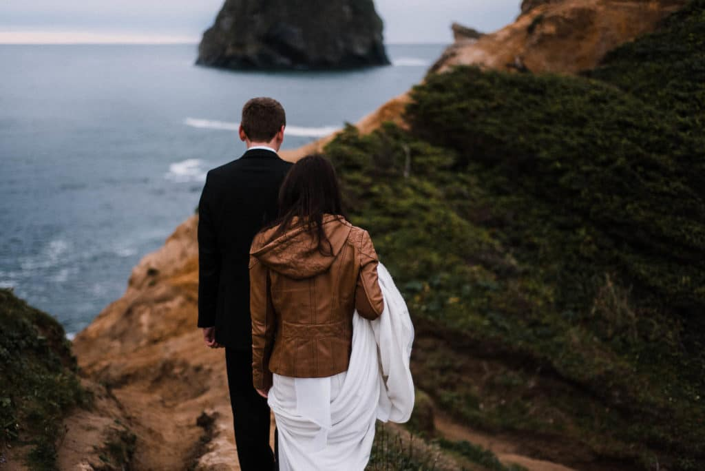 Bride and Groom hiking on Cape Kiwanda Oregon Coast