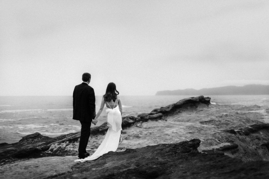 black and white photo bride and groom holding hands Cape Kiwanda Oregon Coast