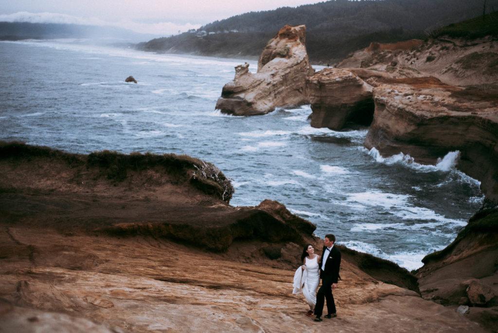 bride looking at groom while walking uphill at cape kiwanda oregon coast