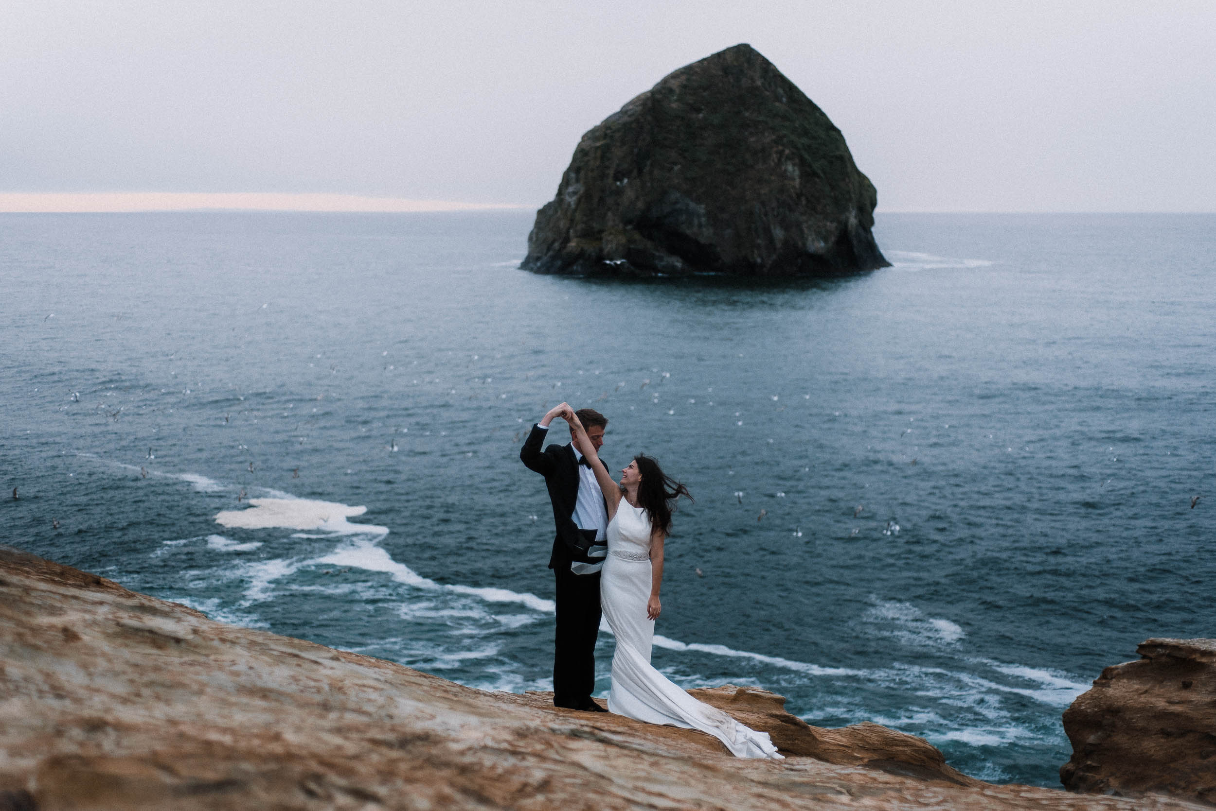 bride and groom dancing on cape kiwanda oregon coast