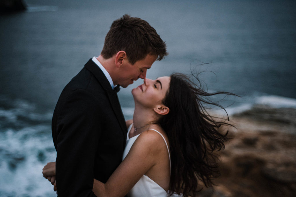 bride and groom touching noses at cape kiwanda