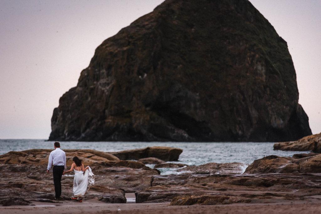 bride and groom walking towards ocean on beach at cape kiwanda