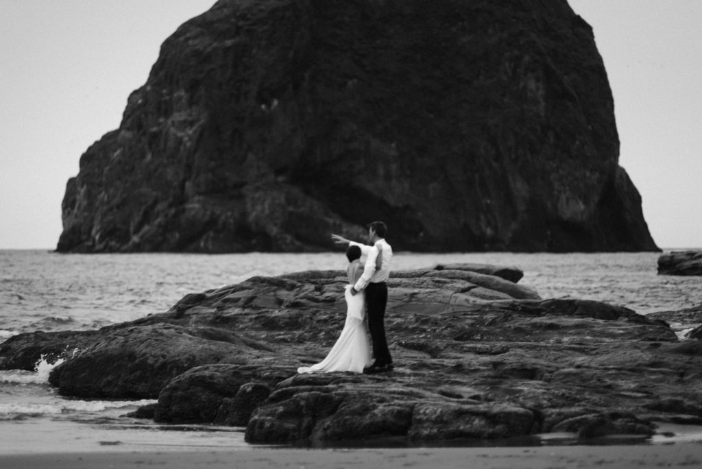 groom pointing with bride on beach at cape kiwanda