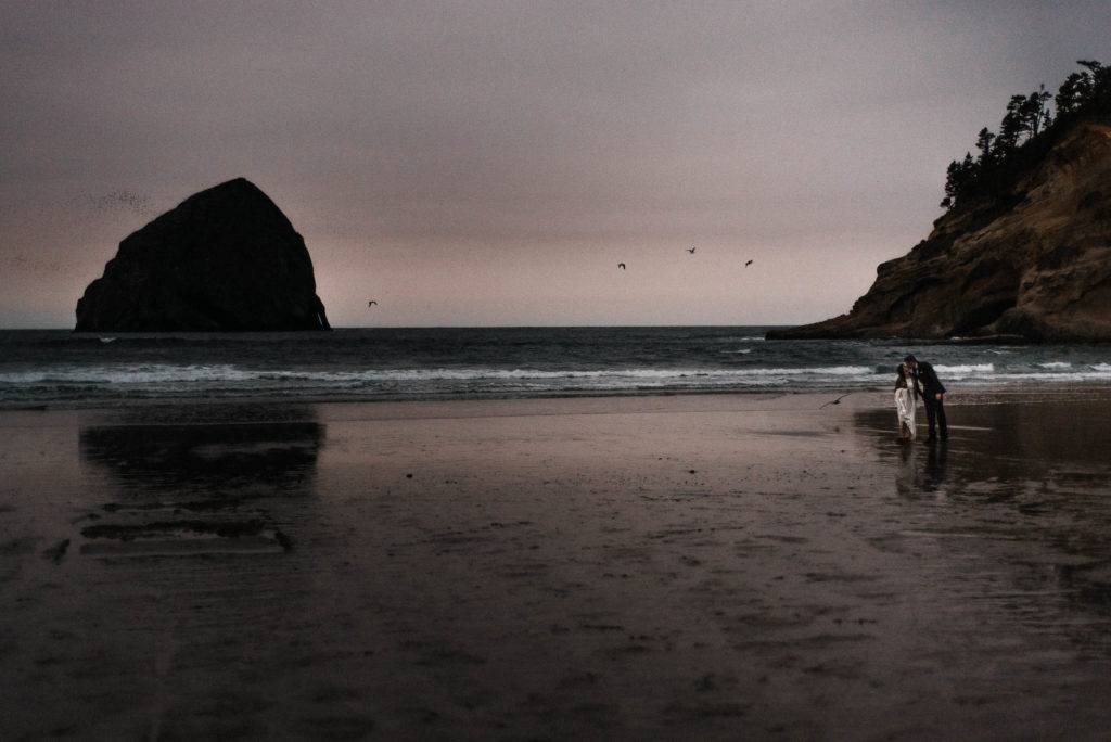 bride and groom walking on beach at sunset cape kiwanda