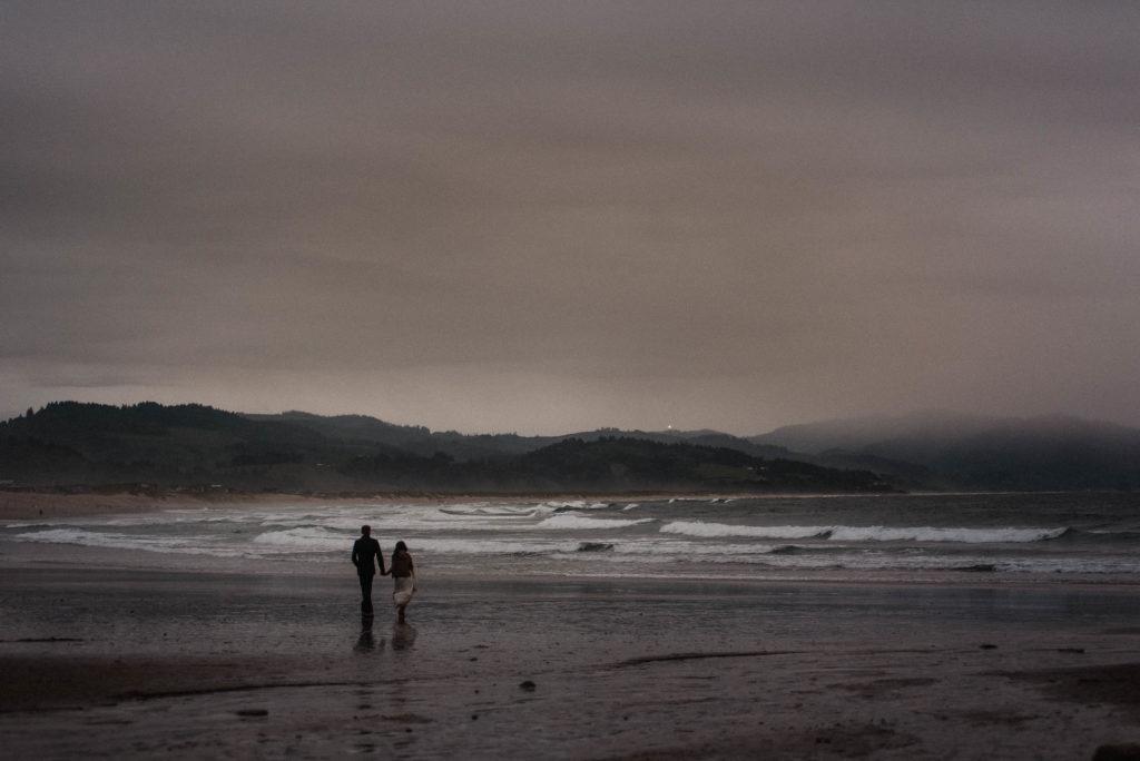 bride and groom walking on beach at sunset cape kiwanda