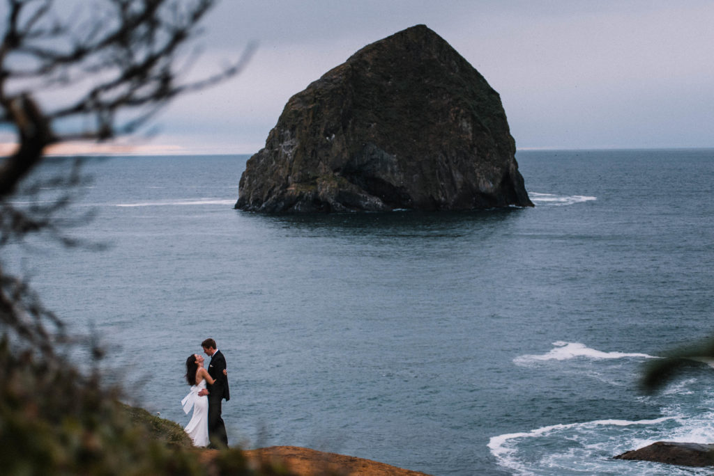 Bride and Groom standing in distance on Cape Kiwanda Oregon Coast