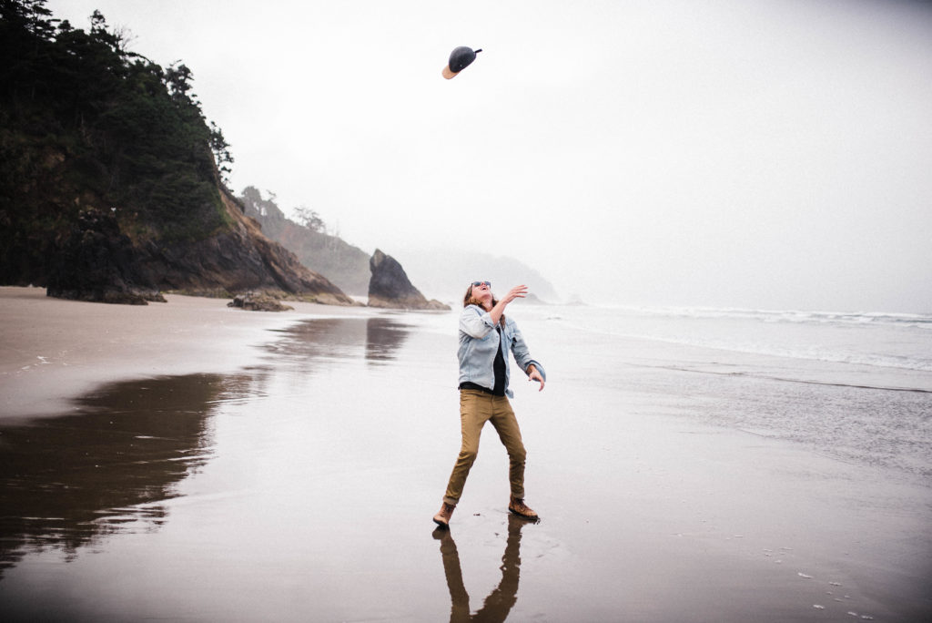boy throwing hat in air hug point oregon coast beach