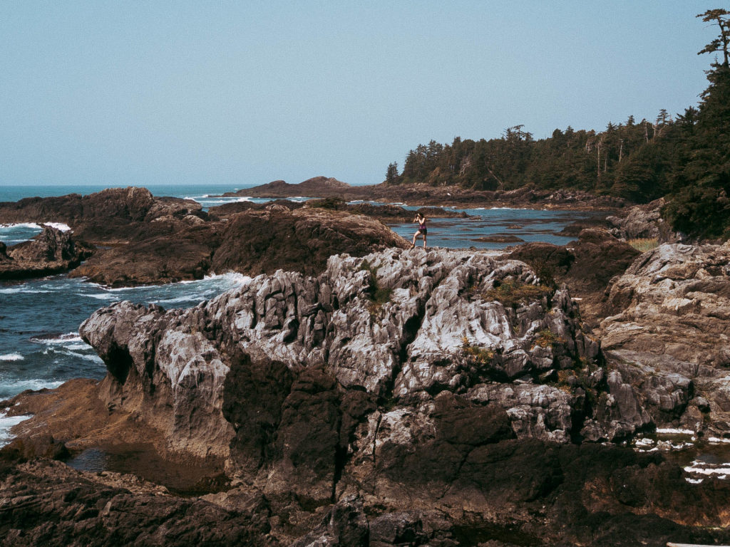 Photographer taking picture from a rock on the wild pacific trail in ucluelet, BC