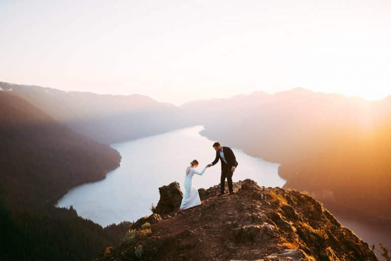 Groom helping Bride up rock on an adventure elopement sunset