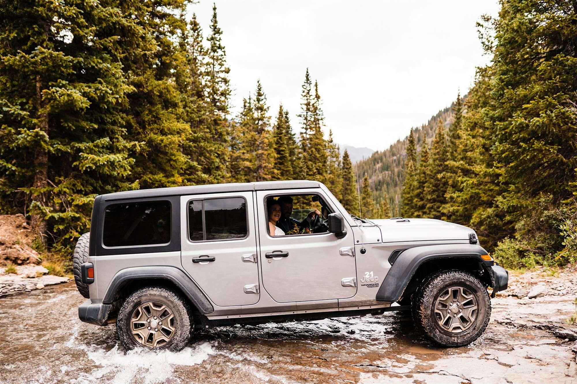 wedding couple crossing river in jeep in colorado
