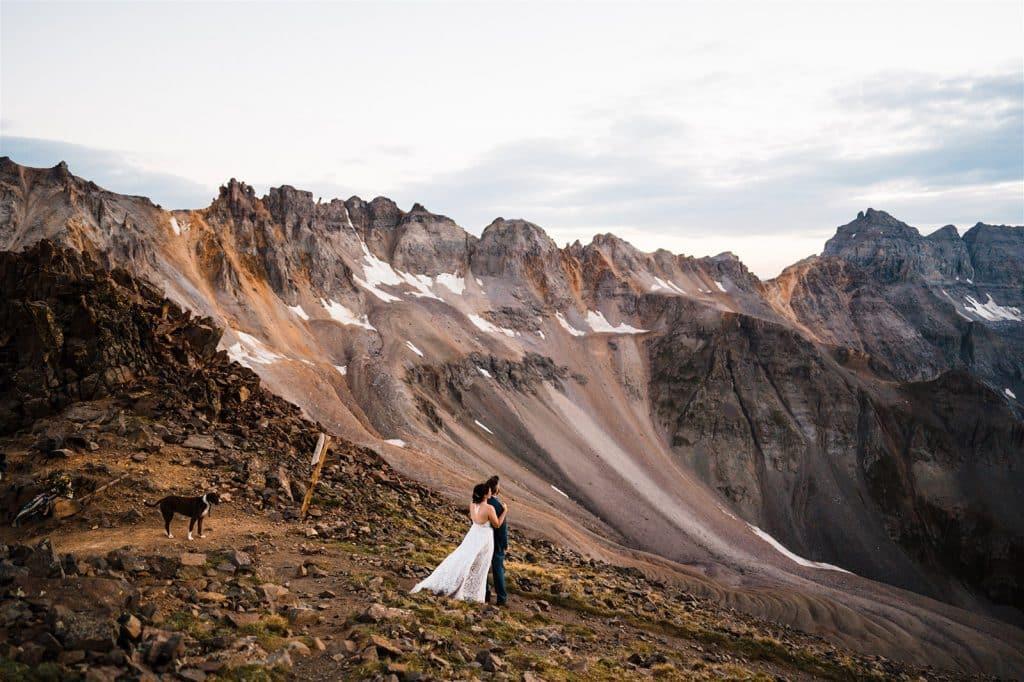 Wedding couple standing atop a mountain on a colorado elopement