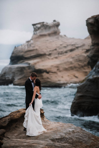 Married couple standing by ocean Cape Kiwanda wedding photography adventure session Oregon Coast