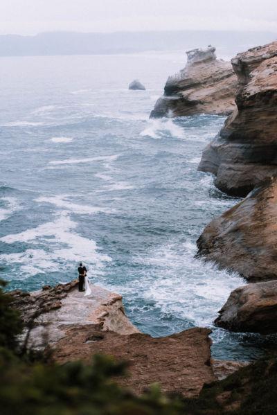Wide shot of Bride and Groom by ocean at Cape Kiwanda Oregon Coast