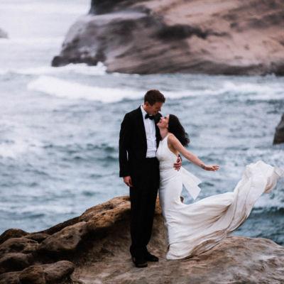 Bride's wedding dress blowing in wind on Cape Kiwanda Oregon Coast