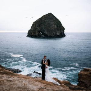 bride and groom standing on cape kiwanda with haystack in background