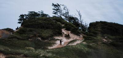 Married couple hiking Cape Kiwanda Oregon Coast