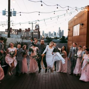 bridal party jumping seattle skyline in background withinsodo wedding